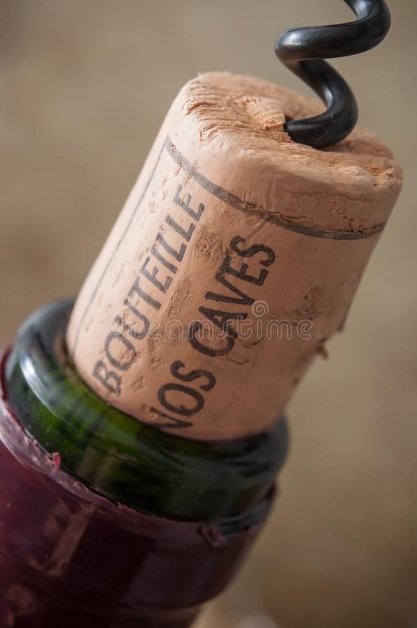Corks wine on wooden background with french text. Closeup of corks wine on wooden background with french text `mis en bouteille dans nos caves` traduction of stock photo