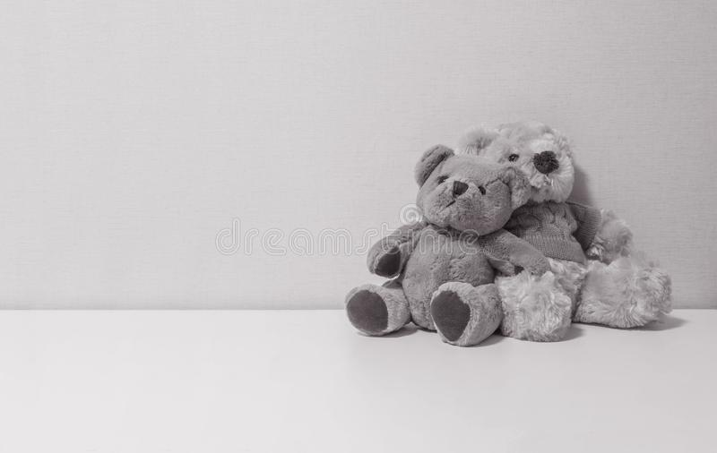 Closeup couple of bear doll on white desk and wall textured background in black and white tone with copy space royalty free stock photos