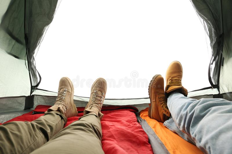 Closeup of couple in camping tent on white background. View from inside royalty free stock image