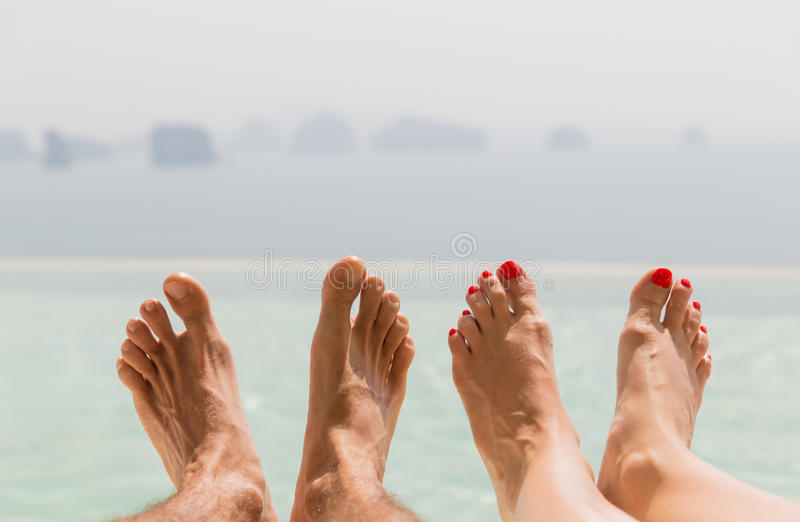 Closeup of couple feet over sea and sky on beach royalty free stock photography