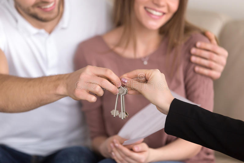 Closeup of couple getting keys to own apartment, property purcha stock images