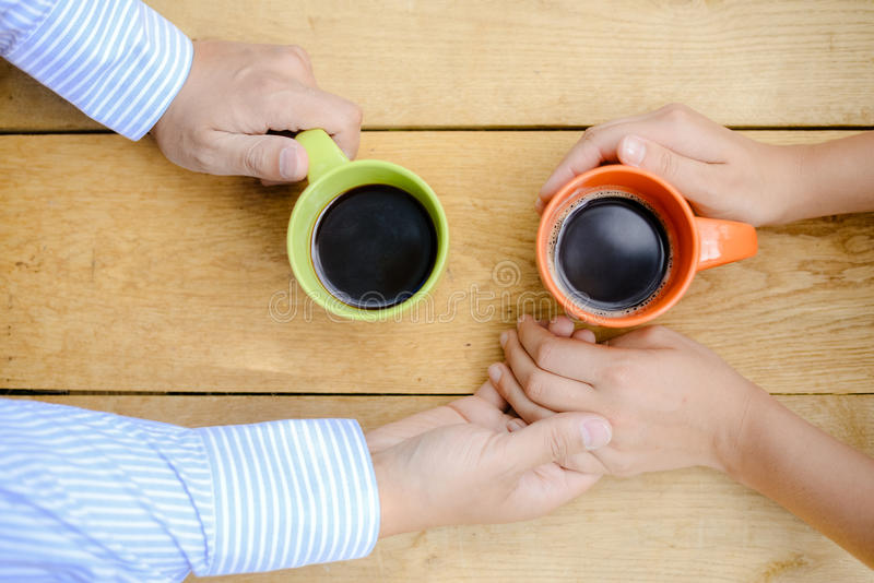 Closeup of couple holding hands with coffee mugs stock images