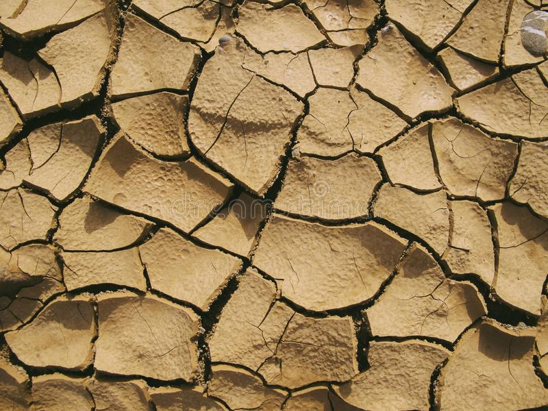 Closeup of cracks in dry soil on a sunny day. A closeup of cracks in dry soil on a sunny day stock image