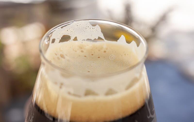 Closeup of craft beer foam in elegant glass stock photography
