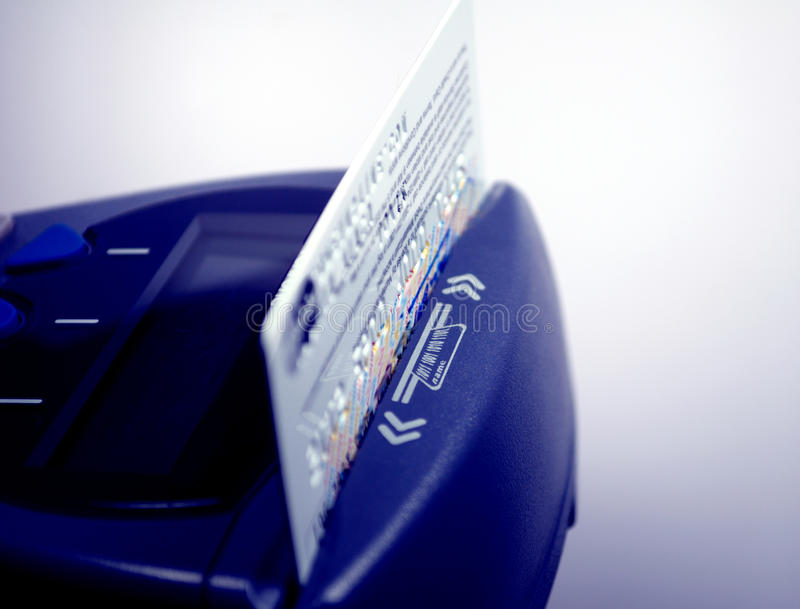 Credit card and pos terminal. POS terminal and credit card close up - blue mood technological color cast royalty free stock photo
