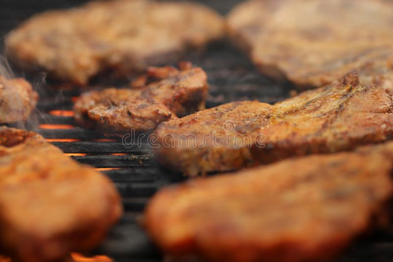 Closeup on crispy grilled meat on smoking hot cast-iron grate with flames underneath. Realistic food and barbecue party concept - foreground and background stock images