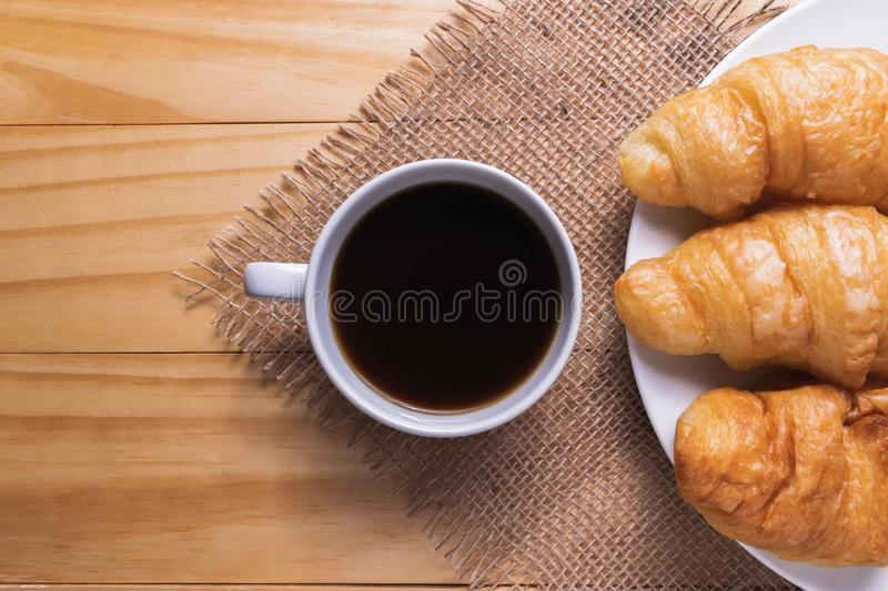 Closeup croissant with coffee on wooden table. breakfast concept royalty free stock photo