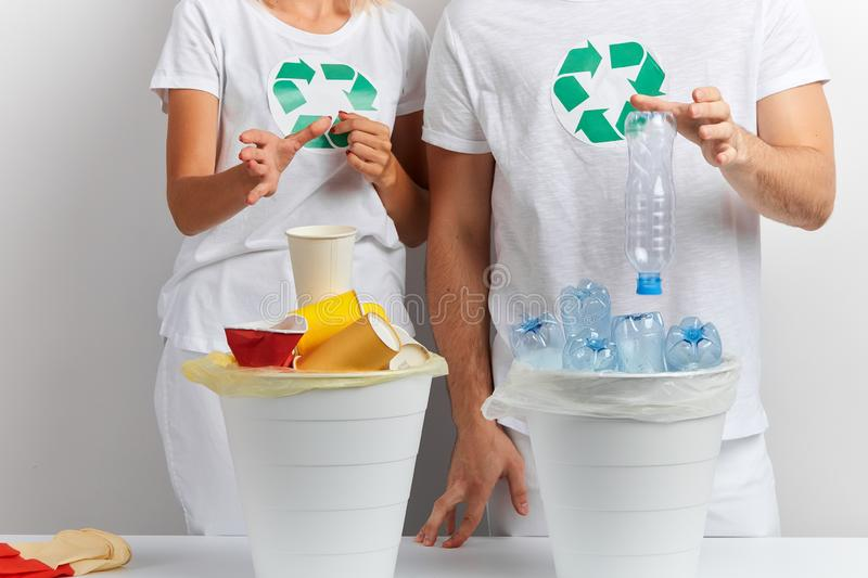 Hands throwing empty plastic bottle, disposable cup in recycling bin. Closeup cropped photo of women and man`s hands throwing empty plastic bottle, disposable royalty free stock photography
