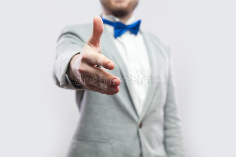 Closeup cropped portrait of handsome bearded man in casual grey suit and blue bow tie standing and giving handshake to greeting, stock images