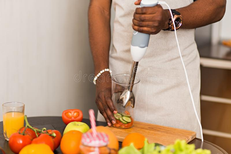 African man preparing healthy food at home in kitchen stock images