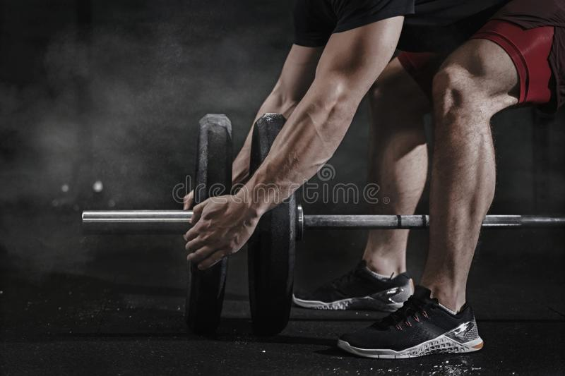 Closeup of cross fit athlete preparing for lifting weight at the gym. Barbell magnesia protection.Handsome man doing functional t. Closeup of cross fit athlete royalty free stock photos