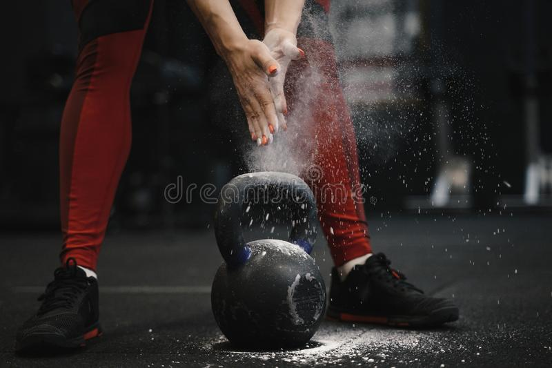 Closeup of crossfit female athlete claping hands with cloud of dust while magnesia protection. Sports woman getting ready for kettlebell workout at gym royalty free stock photos