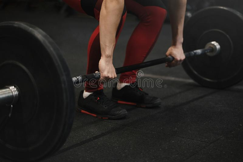 Closeup of crossfit female athlete preparing for lifting weights at the gym. Woman hands holding barbell royalty free stock image