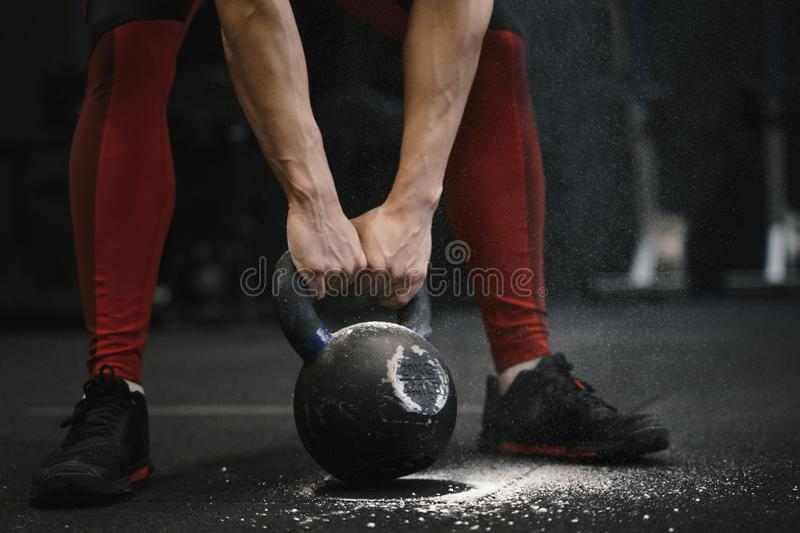 Closeup of crossfit woman lifting heavy kettlebell at gym. Copy space stock images