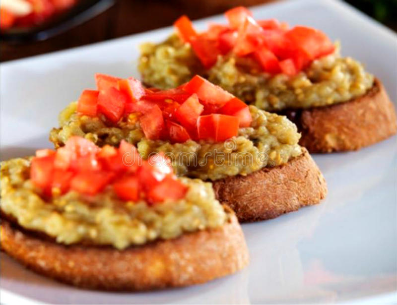 Closeup of crusty bruschetta with eggplants and chopped tomatoes royalty free stock image