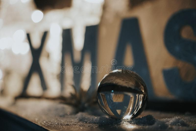 Closeup of a crystal ball near snow with a blurred Xmas text in the background stock photos