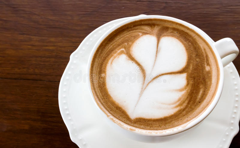 Closeup cup of hot coffee tulip latte art on wood table. stock photo