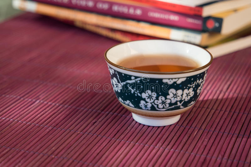 Closeup of a cup of tea and books in an outdoor shaded light stock photos