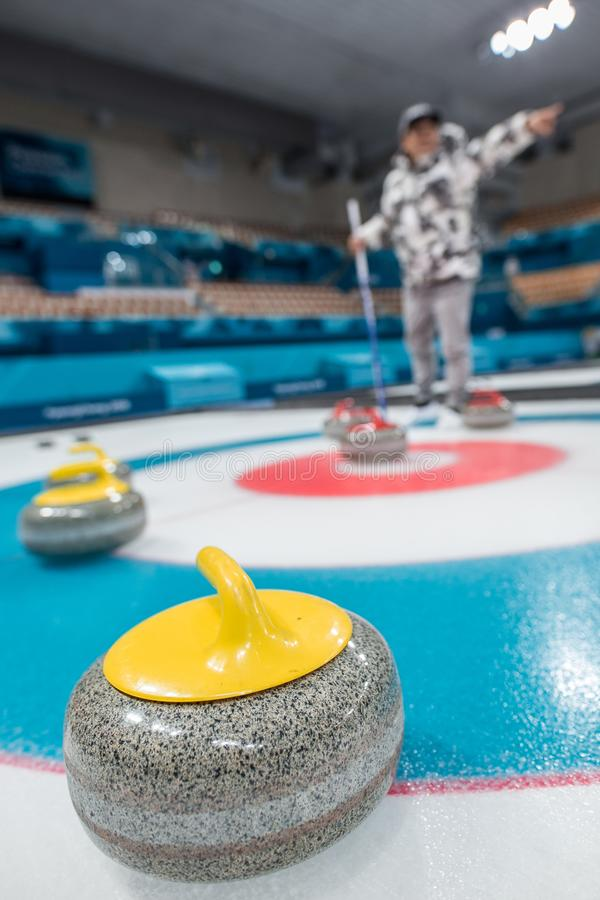 A picture of a person playing curling. stock image