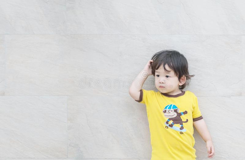 Closeup cute asian kid look at the space with confuse motion on marble stone wall textured background. Closeup cute kid look at the space with confuse motion on stock photo