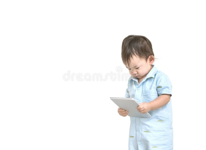 Closeup cute asian kid look at the tablet in his hand with serious face isolated on white background in work concept with copy spa. Closeup cute asian kid look royalty free stock image