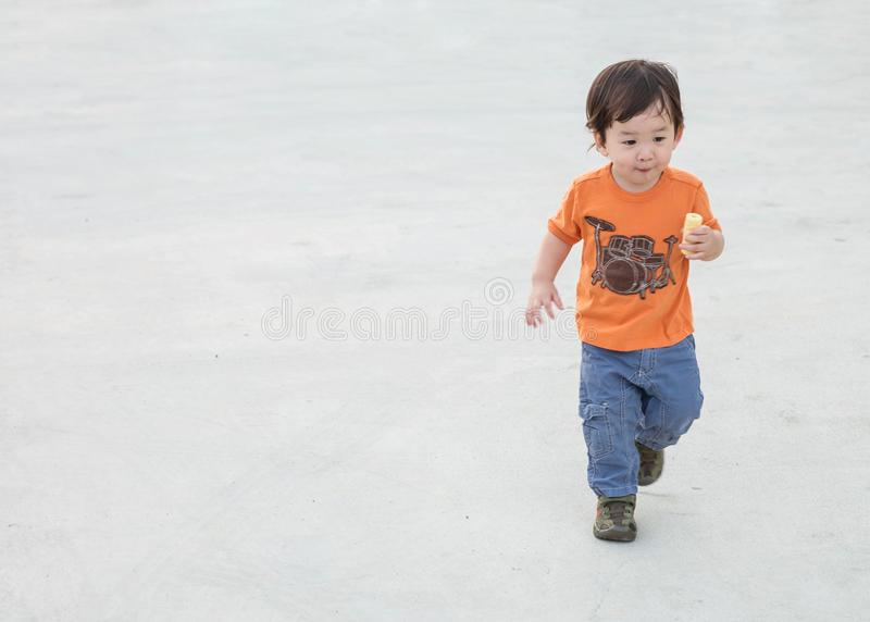 Closeup cute asian kid playing on cement floor at the car park textured background with copy space. Closeup cute asian kid playing on cement floor at the car stock photography
