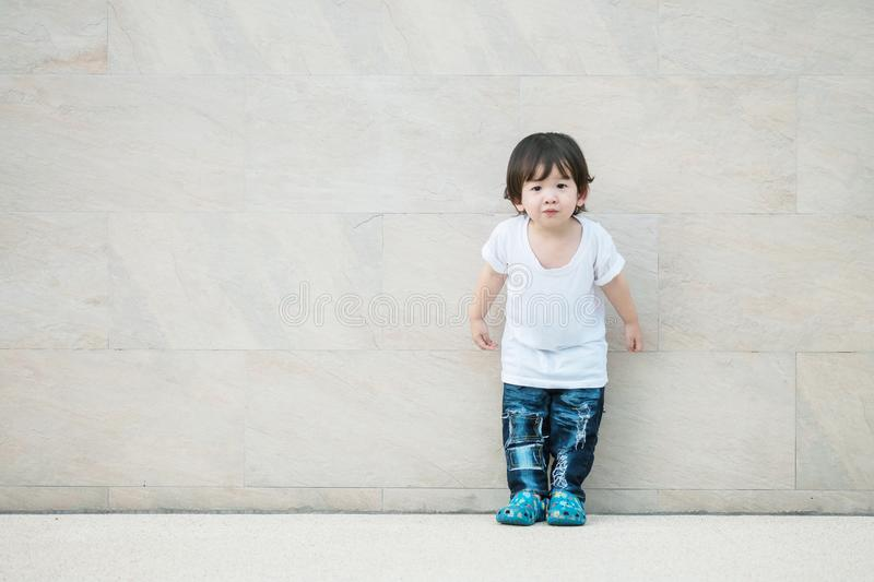 Closeup cute asian kid stand on marble stone wall textured background with copy space. Closeup cute kid stand on marble stone wall textured background with copy stock images