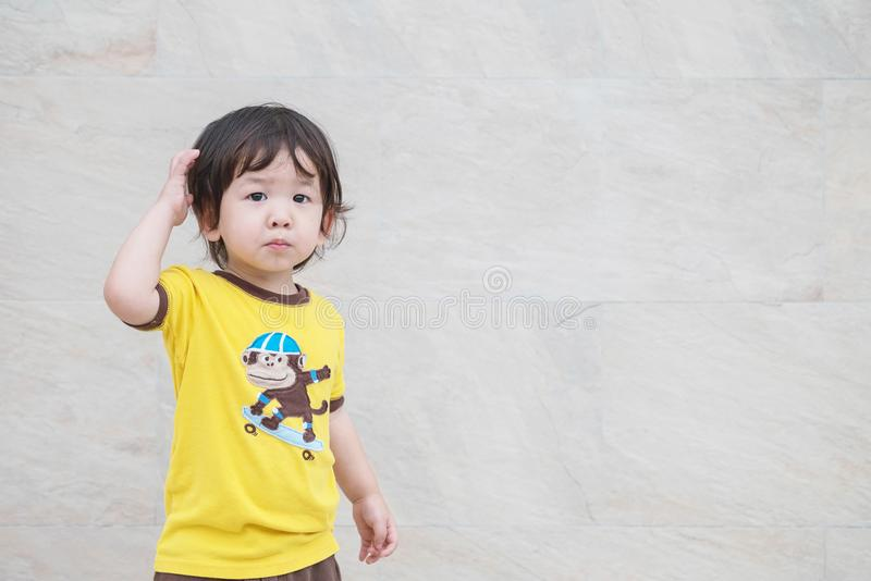 Closeup cute asian kid with confuse motion on marble stone wall textured background with copy space. Closeup cute kid with confuse motion on marble stone wall royalty free stock photography