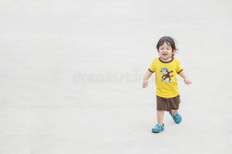 Closeup cute asian kid playing on cement floor at the car park textured background with copy space. Closeup cute kid playing on cement floor at the car park stock photo