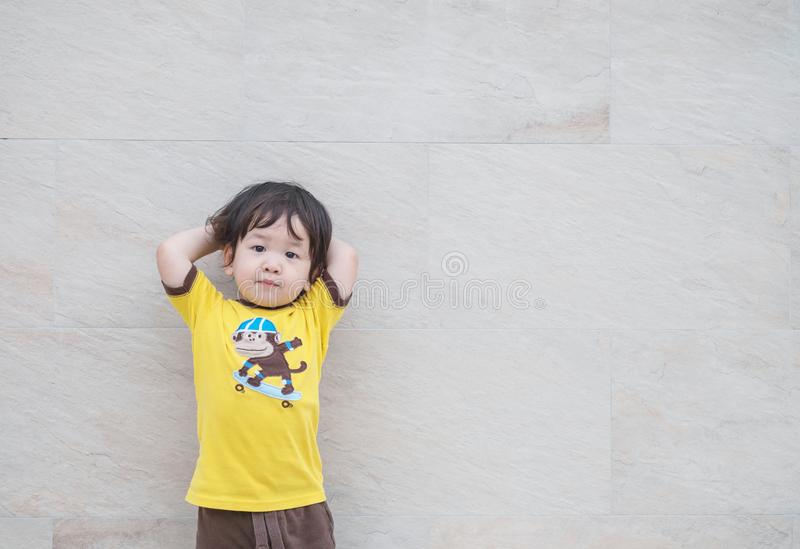 Closeup cute asian kid standing poses on marble stone wall textured background with copy space royalty free stock photo