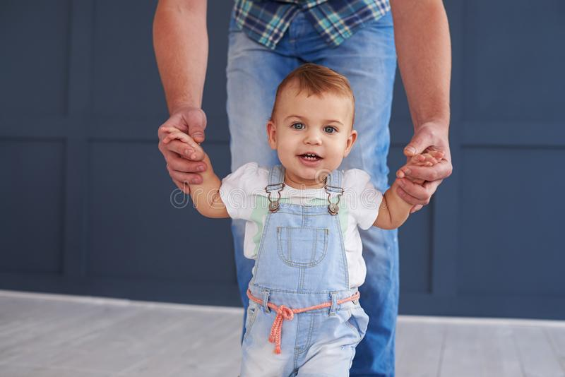 Cute little daughter holding hands of father while doing steps royalty free stock photo