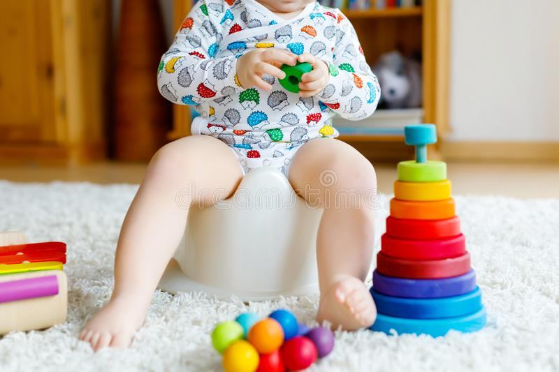 Closeup of cute little 12 months old toddler baby girl child sitting on potty. Kid playing with educational wooden toy. Toilet training concept. Baby learning stock photography