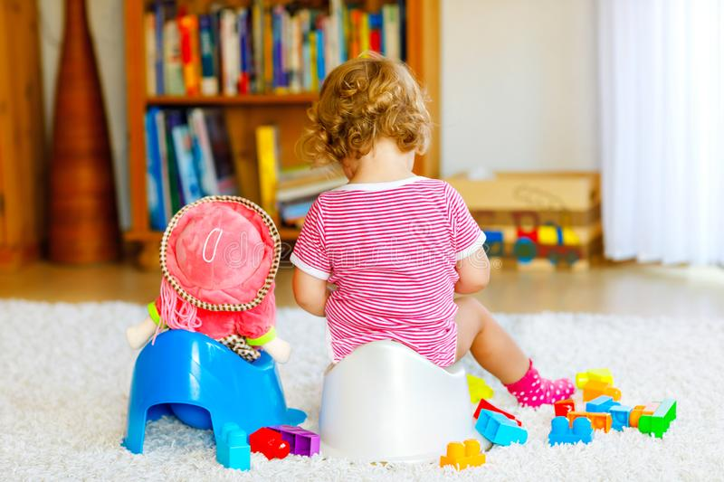 Closeup of cute little 12 months old toddler baby girl child sitting on potty. Kid playing with doll toy. Toilet stock photos