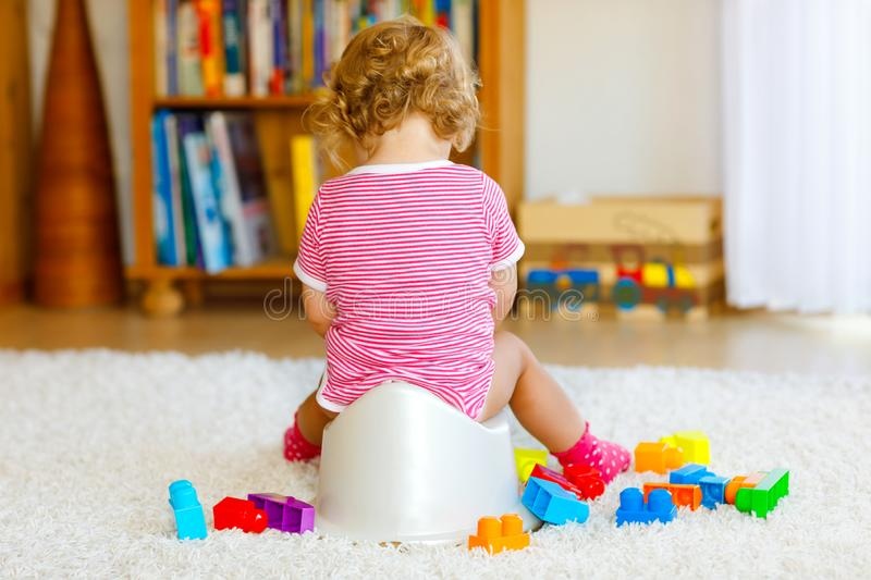Closeup of cute little 12 months old toddler baby girl child sitting on potty. Kid playing with educational wooden toy stock photography