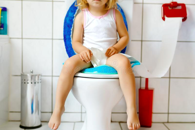 Closeup of cute little toddler baby girl child sitting on toilet wc seat. Potty training for small children royalty free stock photos