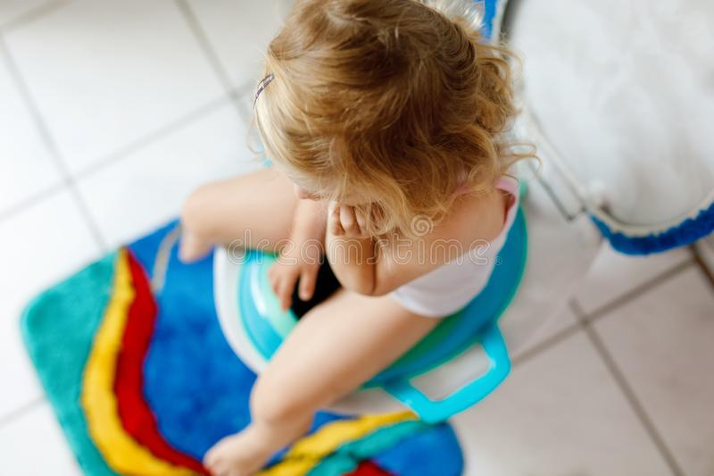 Closeup of cute little toddler baby girl child sitting on toilet wc seat. Potty training for small children stock photos