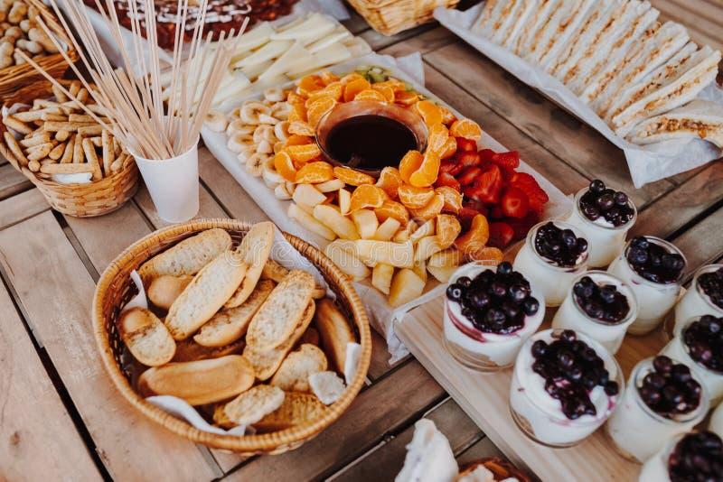 Closeup of cutting board with sandwiches, donuts, yogurt, fruits chocolate fondue tangerine, banana, kiwi, blueberries, royalty free stock photos