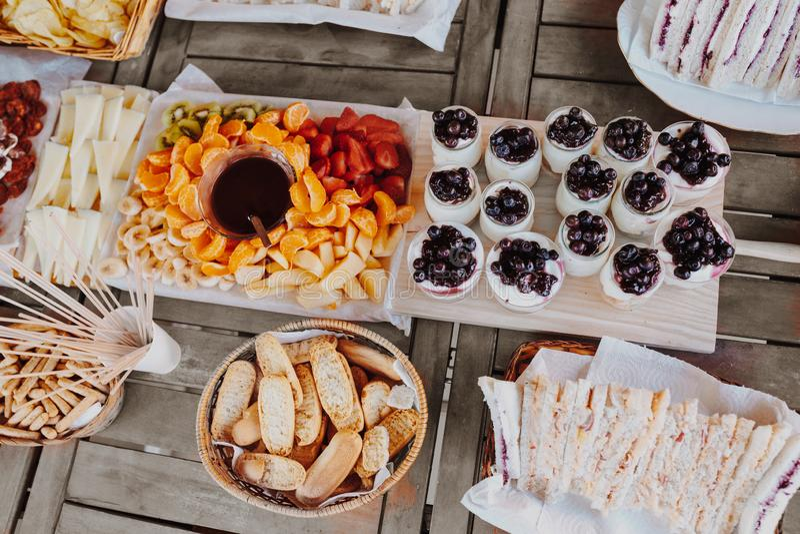Closeup of cutting board with sandwiches, yogurt, fruits chocolate fondue tangerine, banana, kiwi, blueberries, strawberries on a stock photo