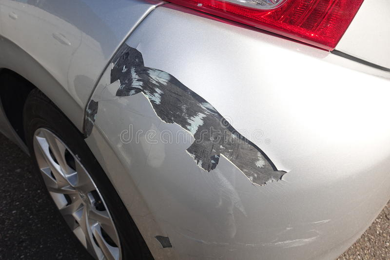Closeup of damage to car. Closeup of damage to bodywork of saloon car with silver (gray) paint scraped off rear wing, wheel and wheel trim visible stock image