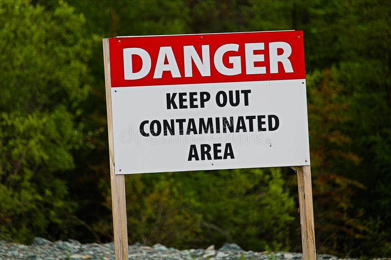 Closeup of a danger keep out of contaminated area sign stock photos