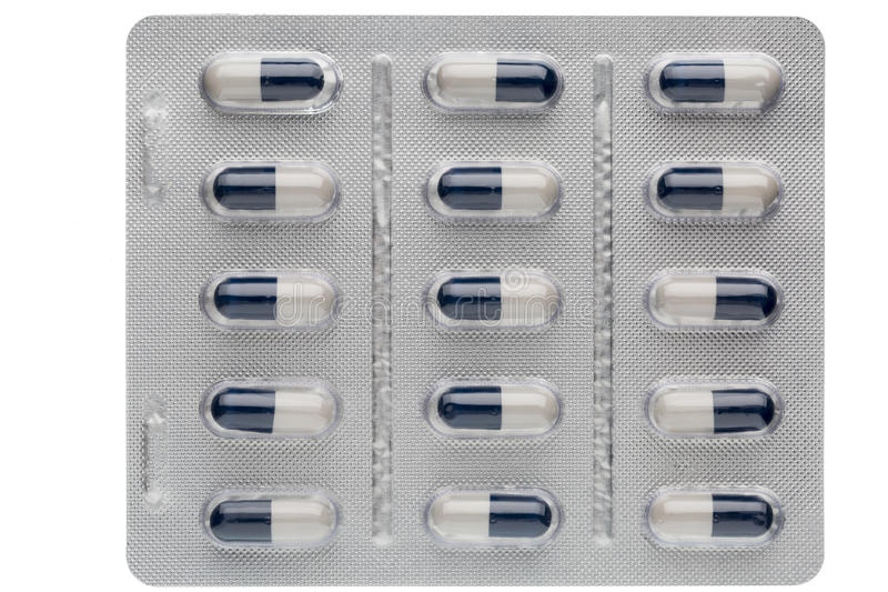 Closeup dark blue and white capsules in medication blister packs royalty free stock images