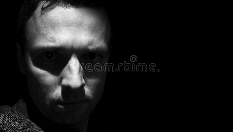 Closeup dark portrait of young adult man royalty free stock photo