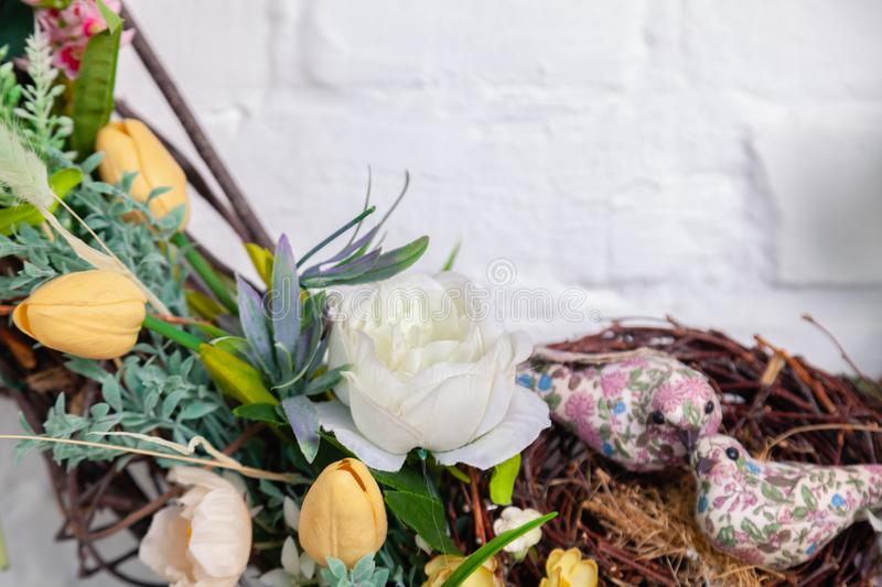 Closeup decor for photo studio interior, spring rods knitting in circle, braided with fresh flowers, roses on the white brick wall stock photography