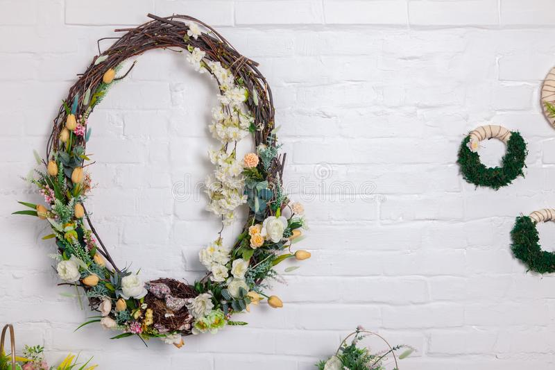 Closeup decor for photo studio interior, spring rods knitting in circle, braided with fresh flowers, roses on the white brick wall. Closeup wreath, decor for royalty free stock photo