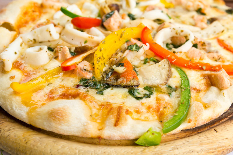 Closeup delicious pizza with seafood. On wooden stand royalty free stock photos