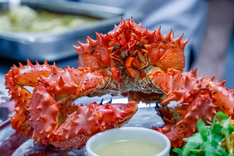 Closeup of delicious tasty boiled freshly prepared red king crab on metal dish with lemon, greens, sauce. Concept expensive food, stock photography