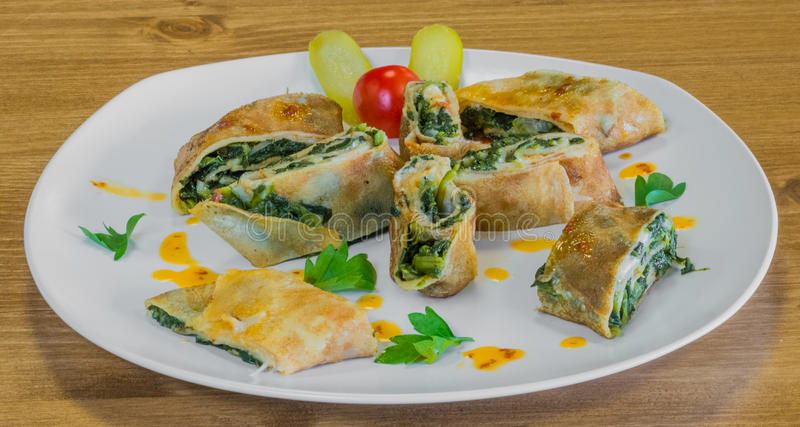 Closeup of delicious wrapped crepe with spinach and pickles beside royalty free stock images