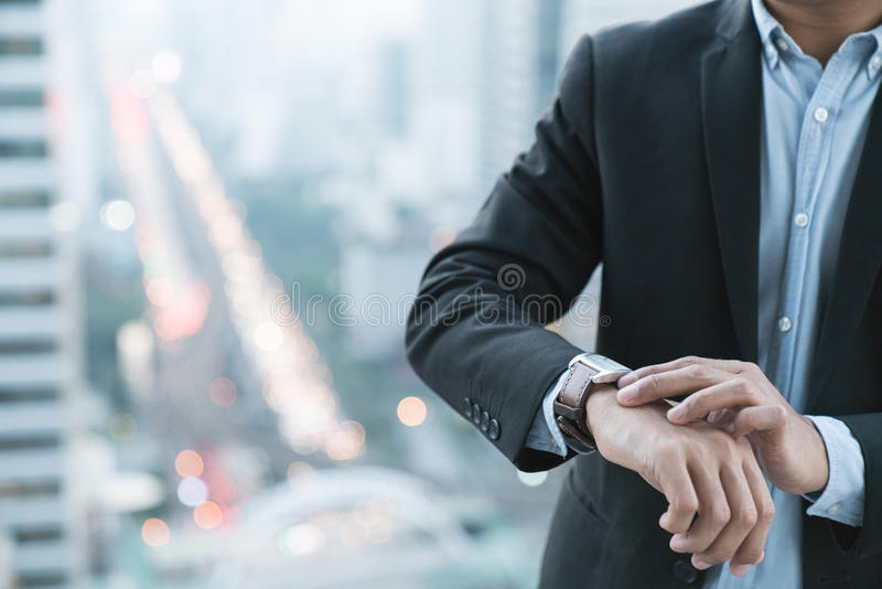 closeup designer watch on businessman hand, he looks on the time royalty free stock images
