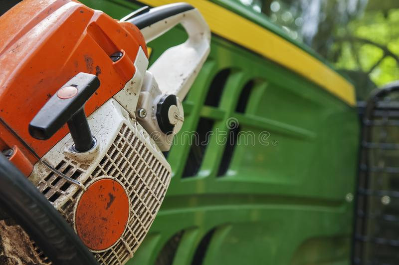 Closeup detail of chainsaw next to tractor in background. Closeup detail of orange and white chainsaw next to green and yellow tractor in background royalty free stock photo