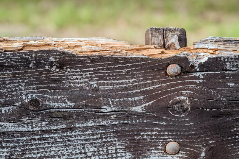 Closeup detail of a coarse weathered and broken part of a rustic wood bench with aged, cracked surface stock image